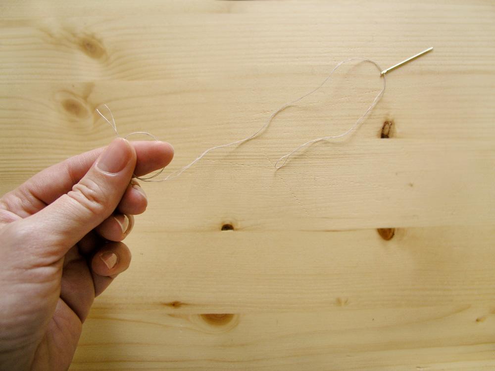 Enhebrar aguja con hilo doble