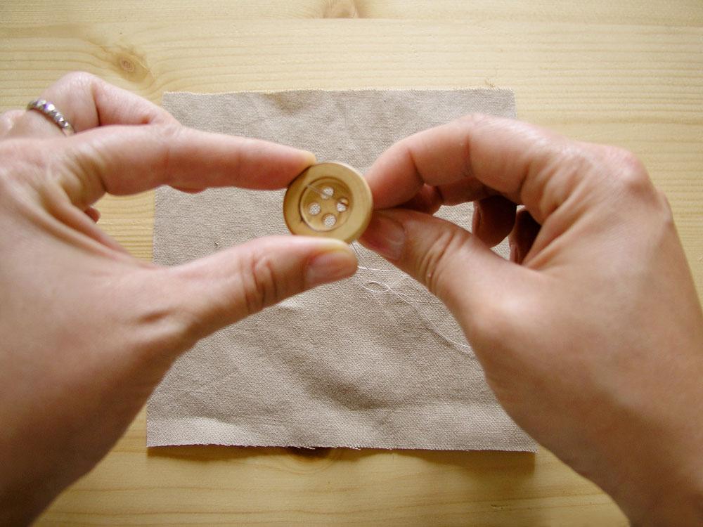 Meter aguja por el primer agujero del botón