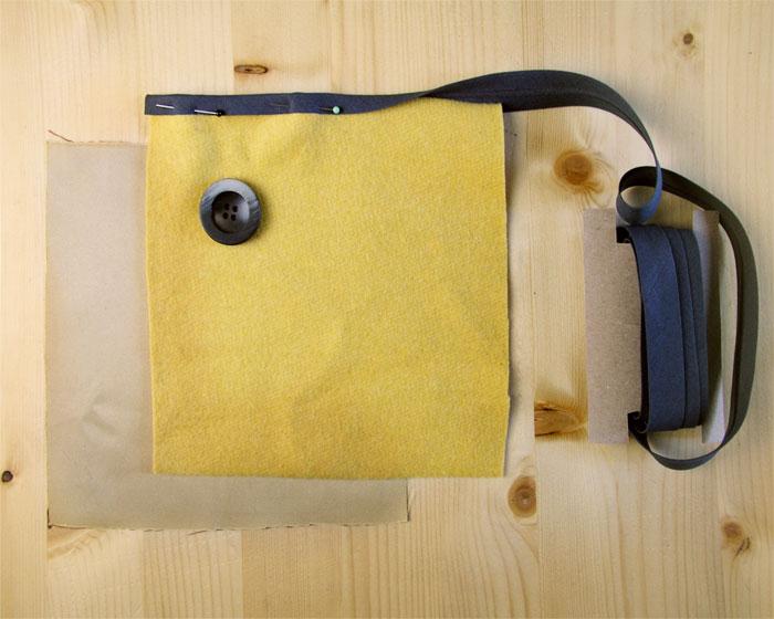 Tejido amarillo con cinta al bies negra y botón grueso y oscuro