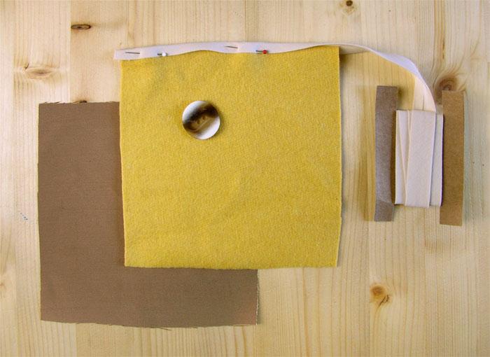 Tejido amarillo con cinta al bies crema y botón bicolor