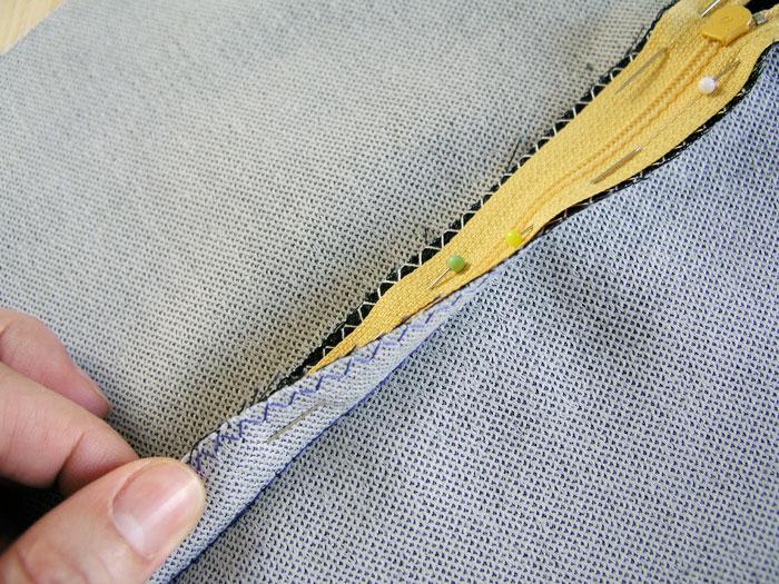 Prender con alfileres la cinta de la cremallera a los márgenes de costura.